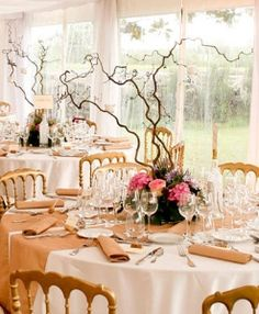 Tall branches with floral arrangement at base as wedding centerpieces. | Belathée Photography
