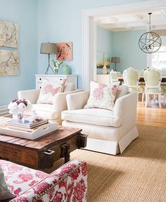 living rooms - turquoise aqua blue walls paint color jute living rug white armchairs rustic wagon coffee table nailhead trim pink chair branch lamp