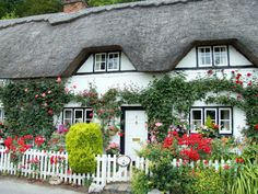 Cottage House Style: Wherwell Cottage -  charming home  in a small village near Andover, Hampshire, England. White picket fence, thatched roof, blooming shrubs and ivy-covered walls...sigh :)