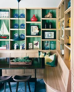 Vibrant and rich, these colors will envelop you in tones of turquoise blue, ruby red, or emerald green. These shades bring a worldly charm to the setting.    Bold emerald green adds a bright and surprising twist in these open kitchen shelves, made of cerused white oak.