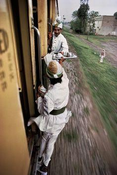 Breakfast tea being passed between cars on the railway between Peshawar and Lahore, Pakistan. Steve McCurry photographer.