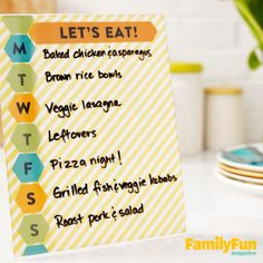 """This refreshingly low-tech message board answers that daily question, """"What's for dinner?"""" Trim scrapbook paper to fit an acrylic sign holder (we got ours at an office supply store). On sheets of card stock, use a computer to print a heading, such as """"Let's eat!"""" plus a letter for each day of the week, and cut them out as shown. Use a glue stick to attach them to the scrapbook paper, then slide the page into the sign holder. With a dry-erase marker, write each week's menu on the board."""