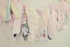 fabric garland created by tearing strips of fabric, lace, and ribbon and tying them onto a long strip of twine, with embellishments like buttons, charms, and drapery clips to hang photos and mementos