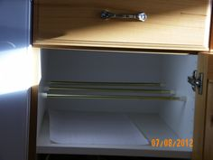 Three tension rods used to hold up cookie sheets