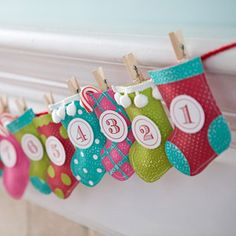 """""""Stocking Garland Advent Calendar: Design by Erin Roe    A garland made of 24 hand-cut stockings makes a quick and fun project for you and your children. Adhere two stocking shapes together, and pad the inside of each stocking with some cotton balls to give it a fuller look but allow room to hold a treat or note. Then use clothespins to attach the stocking to a length of yarn."""""""