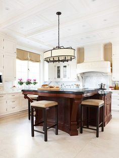 """This island takes center stage with the spectacular chandelier to top it all off!  This custom island works so well even though it is significantly bold.  This was accomplished by keeping the background cabinets and countertops light and neutral, which prevents the island from being too """"weighty"""" for the space. Gorgeous!  Better Homes  gardens"""