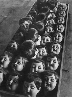 Row of dolls heads during production, Germany, 1950. S)