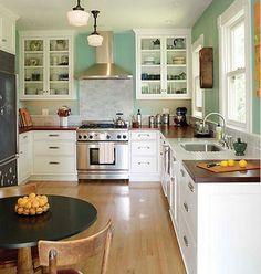 Wood countertops, white cupboards, white subway tile backsplash, blue walls.
