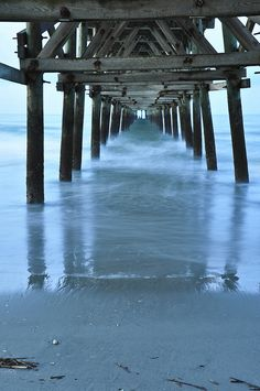 ocean waves washing up under the pier