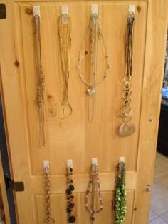 Command Hooks on the inside of the bathroom cabinet to organize jewelry - I need to do this!