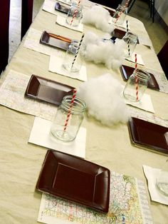 "Map placemats and cotton ""clouds"" at travel or airplane themed party"