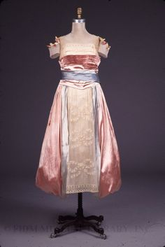 Lucile dress in light pink with a pouf/bubble skirt unusual for the period, and embellished with applique fabric flowers and inset lace bows; c. 1917
