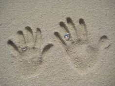 hand prints in the sand with wedding rings <3