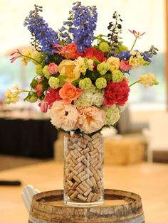 Unexpected Centerpiece Idea: A Wine-Cork Vase    Add extra personality to a plain cylinder vase with stacked-up wine corks.