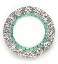 A diamond and chrysoprase circle brooch, circa 1940 composed of old European-cut diamonds accented by single-cut diamonds; estimated total diamond weight: 5.00 carats; mounted in platinum; diameter: 1 7/16in. (pin finding in fourteen karat white gold)