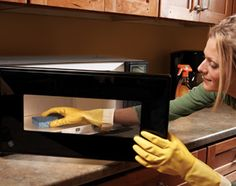 Heat sponge in the microwave first    Grease and dirt build up on kitchen cabinets over time. To clean your cabinets, first heat a slightly damp sponge or cloth in the microwave for 20 to 30 seconds until it's hot. Put on a pair of rubber gloves, spray the cabinets with an all-purpose cleaner containing orange oil, then wipe off the cleaner with the hot sponge.