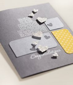 Glitter paper hearts on gray for a sophisticated wedding congrats.