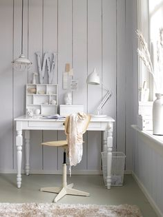 Hanging white industrial lamp over white workspace.