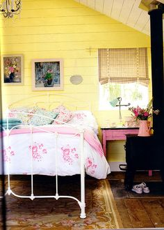 Cottage bedroom - sunny yellow walls and white cast iron bed