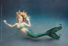 Underwater photograph of a mermaid with a Mertailor tail in sea green.