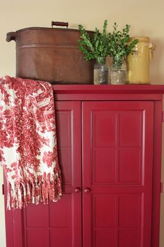 RED cupboard love with fringed red and white accent piece...antique (maybe cooker) atop cupboard....