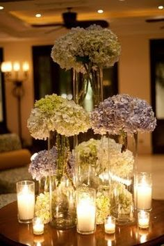 Hydrangeas & candles. This could work with the upside-wine glasses over yellow flowers with candles on top for bring the yellow into the mix.