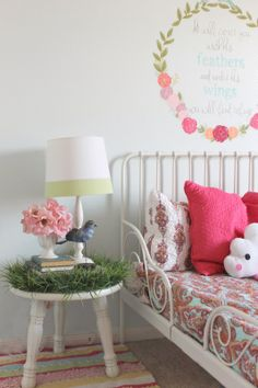 Girls Room Makeover. Grassy nightstand, white metal toddler bed, hand painted wreath with verse painted about bed, bright patterned quilt, and fun cloud pillow. Theraggedwren.blogspot.com