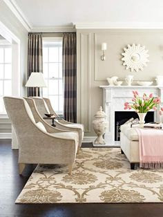 So many things to love in this living room- the rug, those chairs, a sunburst mirror, and a pretty pink throw for a just right pop of color.