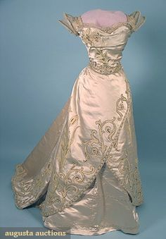 "WORTH PARIS BALLGOWN, c. 1900  2 piece, heavy ivory satin w/ appliques of cream wool challis day lilies decorated w/ gold beads & sequins, Brussels lace bodice trim, B 34"", W 22"", Skirt Front L 44"", Back L 59"", (many small splits in satin, waistband & lining replaced mid 20th C) fair-good."
