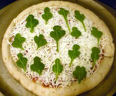 St. Patrick's Day white pizza using spinach leaves as shamrocks.