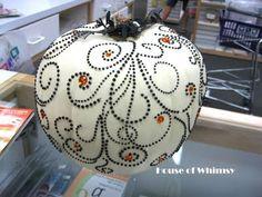 White pumpkin with orange and black swirls of gems.