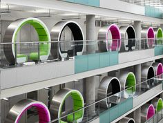 Circular meeting pods line the glass interior walls of the BBC North offices. Large enough to accommodate two people for impromptu meetings, the pods occupy dead space at the edge of the atrium.