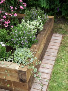 brick edges around the raised garden beds allow easy mowing around the boxes
