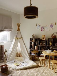 Amazing playroom with Madeline Weinrib Atelier Sand Brooke Rug, oak play table and stools, white teepee, Ikea Rens Pelt, gray linen roman shade and woven storage cubbies.