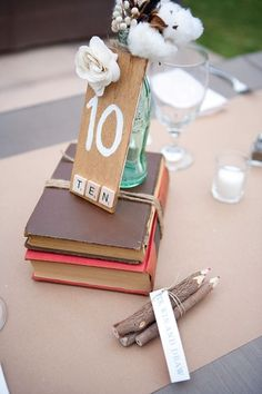 Centerpieces of old books, vintage soda bottles and pencil bundles for guests to write their comments.