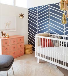 Coral and navy nursery with an Oeuf Sparrow Crib in White. Love the navy herringbone wall