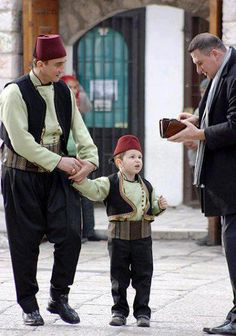 """Bosnian Muslims in their traditional clothes during Eid. The picture shows giving """"Bajram banka""""; money that people give to children on Eid."""