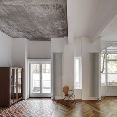 This renovated apartment in Berlin features raw concrete ceilings and floors that combine oak parquet with decorative tiles