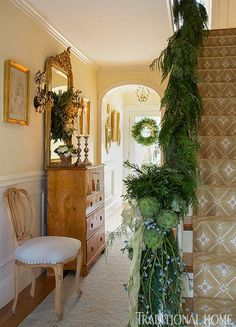 Artichokes and a silver bow are fun trimming on a garland of greenery. - Traditional Home® / Photo: Eric Roth / Design: Tanya Capello