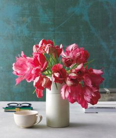 If you constrain tulips (or calla lilies or ranunculus) about two-thirds of the way up with a cylinder vase, the natural arc of their soft stems will take care of the arranging.