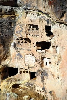 Rooms cut into the side of a cliff. The small arched coves are dovecotes. The people of Cappadocia were agricultural, and they gathered pigeon guano for use as fertilizer. (by hopemeng on Flickr)