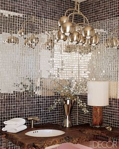 A shimmering retreat where matte and mirror-finish glass tiles wrap around a counter made of a slice of walnut root; the faucet is by Lefroy Brooks.