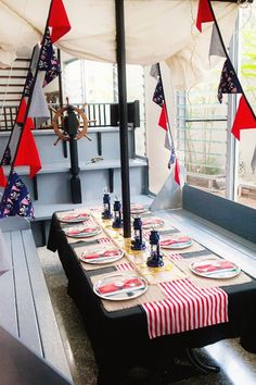 Table decorations - black table cloth, red striped runner and ship flags