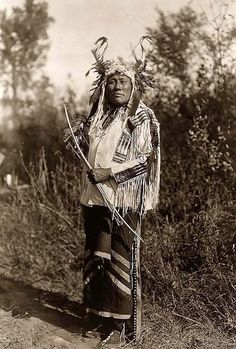 Here for your browsing pleasure is an imposing photo of Long Time Dog. It was made in 1908 by Edward S. Curtis.    The illustration documents the indian in a full-length portrait, standing, facing front, and wearing a headress, buckskin shirt, and leggings with brass bells. He is a holding a Bow and Arrows