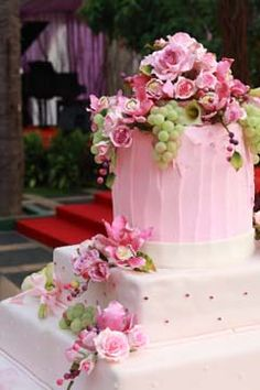 Lovely three tier white and pink buttercream cake. The top tier is pink and round, the bottom two tiers are white with pink polka dots. The cake is decorated with an assortments of pink Peonies and garnished green grapes.