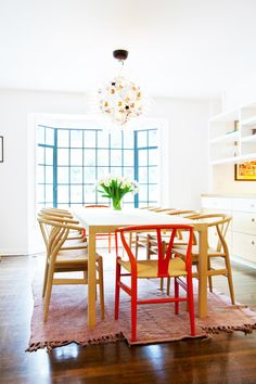 Tour a Bright, Fresh LA Family Home // wishbone chairs, dining room, pine dining table, vintage rug, red chair, glass bulb chandelier