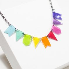 Learn how to make a simple but colourful necklace made out of little banners.