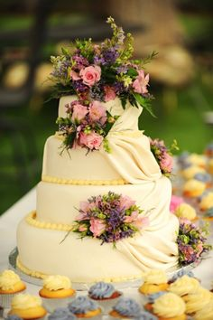 Spring colors, pale yellow with pink, purple and blue cupcakes surrounding a goreous tiered cake