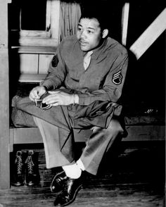 """World Heavyweight champ Joe Louis (Barrow) sews on the stripes of a technical sergeant--to which he has been promoted..."" April 10, 1945"