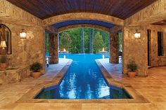 Uniting indoor and outdoor spaces, this pool provides a enclosed area perfect for swimming laps or simply admiring the beautiful stonework. Blue Haven Pools & Spas http://www.luxurypools.com/builders-designers/blue-haven-pools-spas.aspx